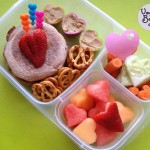 English muffin with cream cheese and banana, pretzels, fruit salad, cucumber and carrots, heart cups filled with hummus for dipping