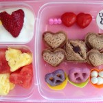 Mini heart pocket sandwiches, yogurt covered pretzels and raisins, coconut milk yogurt, two mini tomato hearts, watermelon and pineapple heart salad